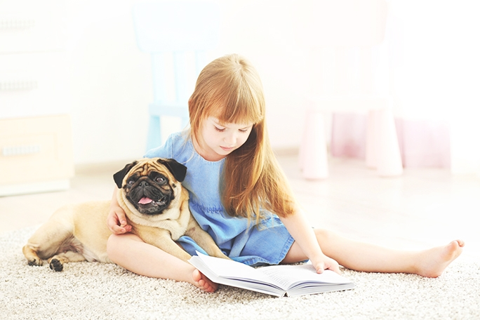 Girl with a pug on carpet